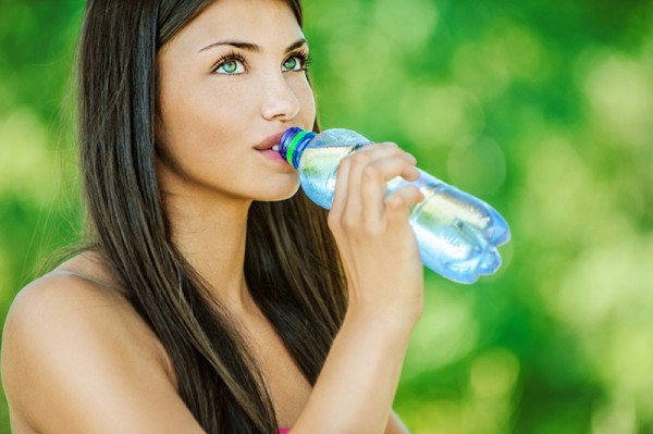 woman with bare shoulders drinks from bottle of water